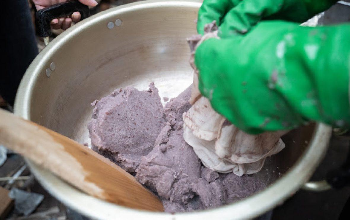 水分を絞った絞り袋の中の小豆を鍋に戻す